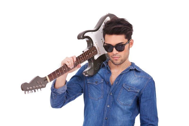 Arroganter junger Mann mit Gitarre lizenzfreie stockfotografie