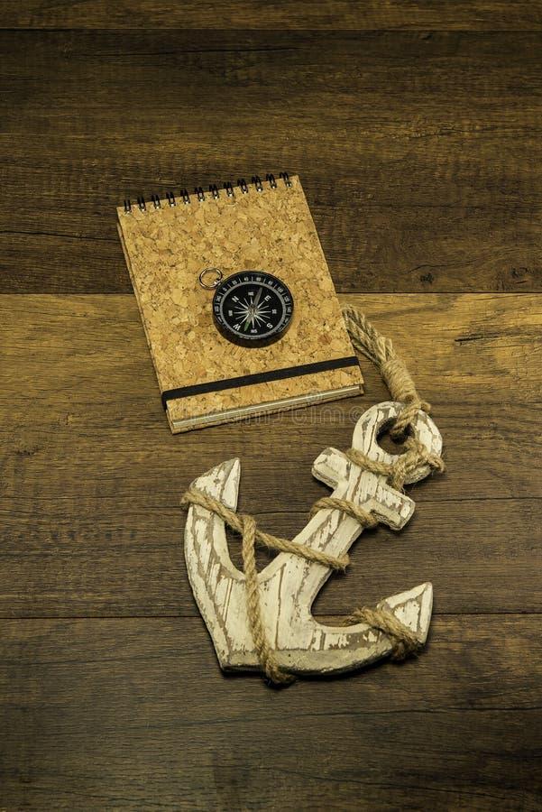 Arrolhe o livro da tampa com compasso e a grande âncora branca velha foto de stock
