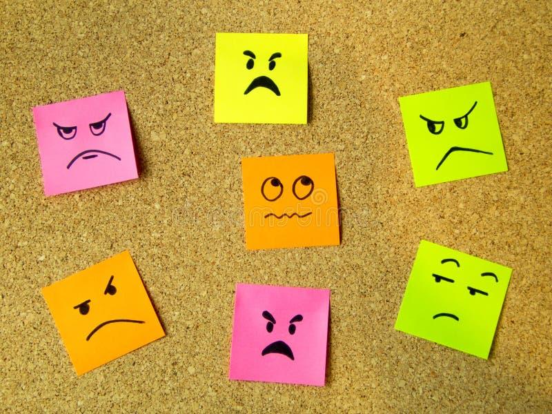 arrolhe a placa com os post-it coloridos que representam vários emoticons com uma comunicação da emoção da raiva que acusa o conc fotos de stock