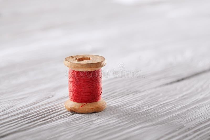 Arrolle con el carrete rojo en el fondo de madera blanco fotos de archivo