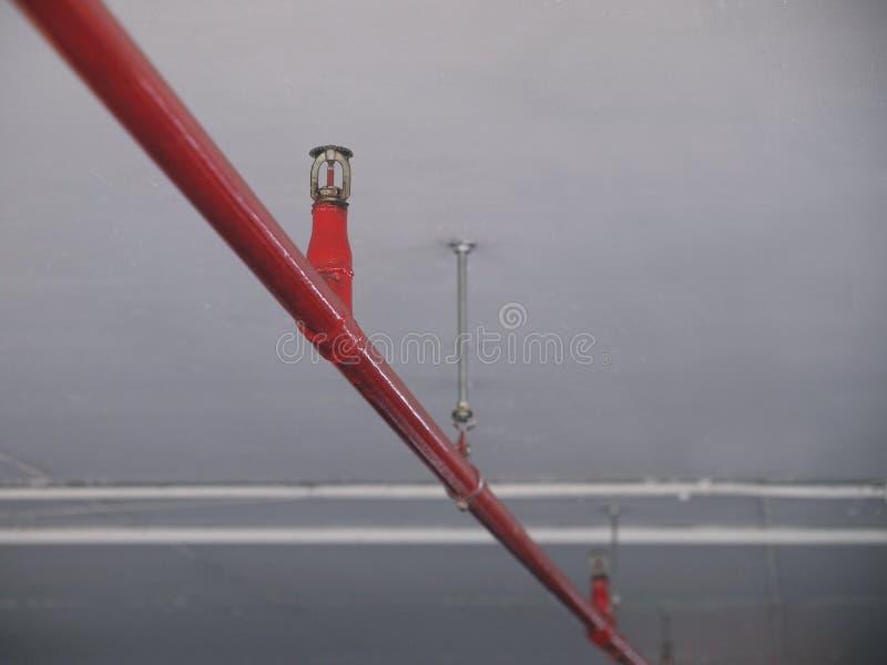 Arroseuse automatique du feu dans le système rouge de conduite d'eau photographie stock