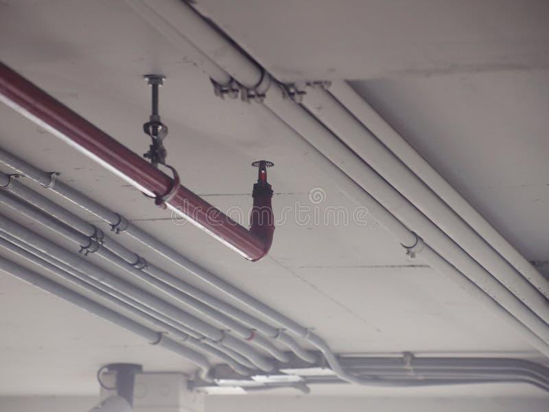 Arroseuse automatique du feu dans le système rouge de conduite d'eau photos libres de droits