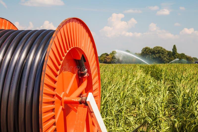 Arroseuse d'irrigation sur des terres cultivables images stock