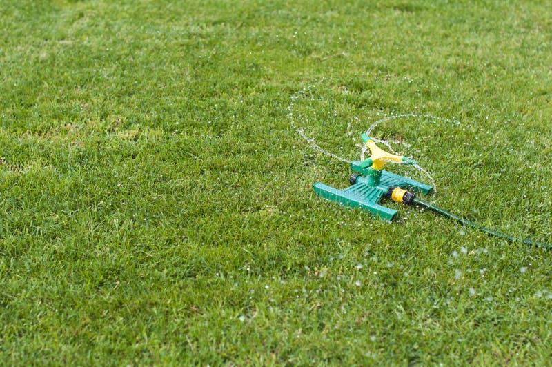 Arroseuse de pelouse au-dessus d'herbe verte photographie stock