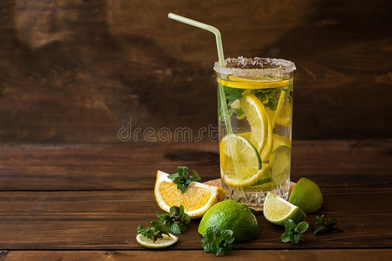 Arrosez avec la chaux, le citron et les feuilles en bon état sur un fond en bois foncé photographie stock