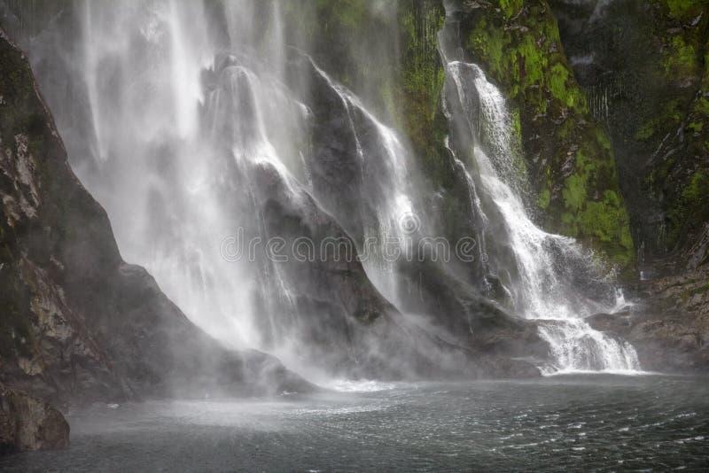 Arrosez cascader en bas des murs raides de fjord, Milford Sound, nouveau Zeala image stock