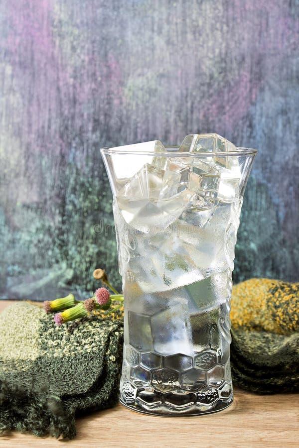 Arrosez dans un verre avec de la glace placée sur la table et le tableau noir en bois photographie stock libre de droits