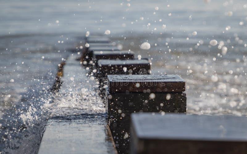 Arrosez de la vague éclaboussant au-dessus du brise-lames dans la baie images stock