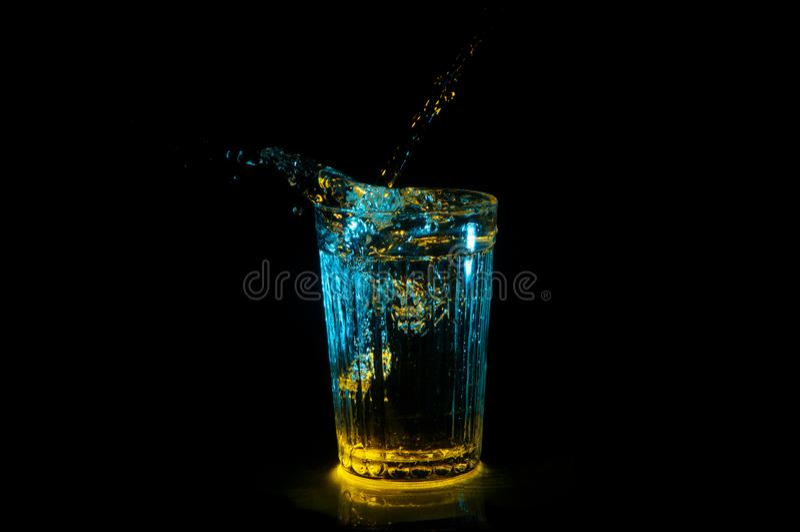 Arrosez l'éclaboussement du verre à boire strié dans les lumières bleues et jaunes d'isolement sur un fond noir image stock