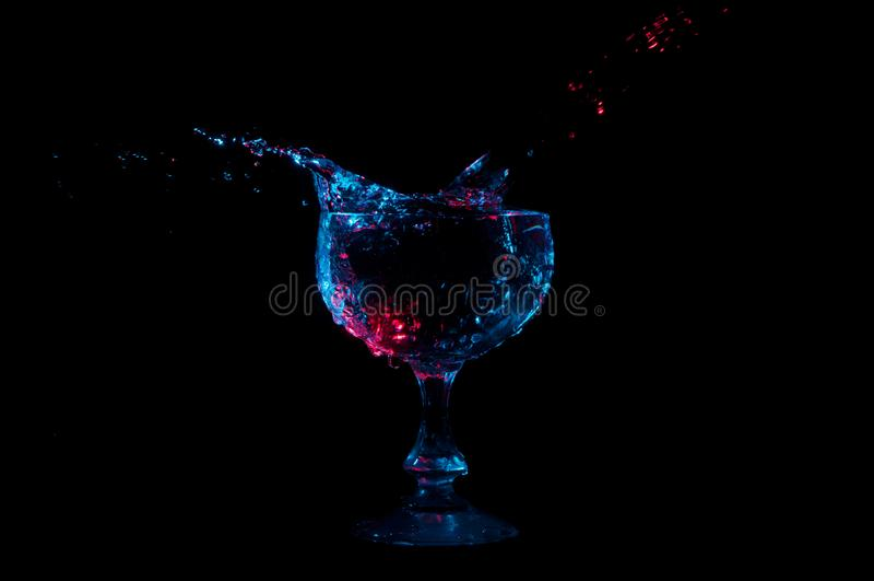 Arrosez l'éclaboussement hors d'un verre formé par gobelet sous les lumières rouges et bleues sur un fond noir photos stock