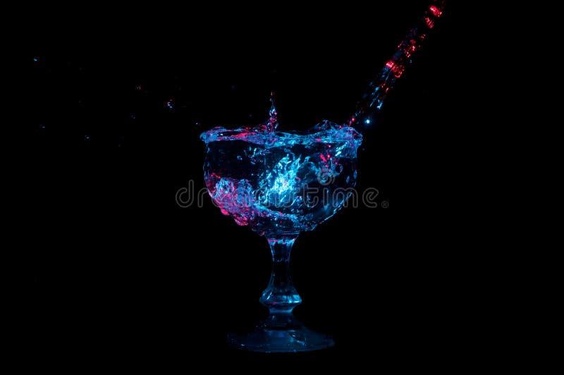 Arrosez l'versement dans un gobelet en verre et en éclaboussant sous les lumières colorées sur un fond noir images libres de droits