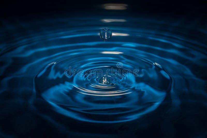 Arrosez la baisse des vagues avec le fond et la réflexion bleus photos stock