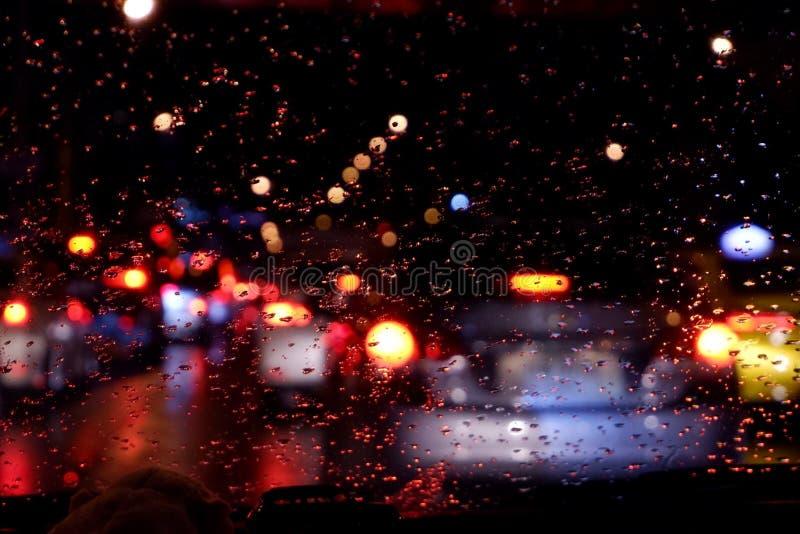 Arrosez la baisse sur le vitrail de voiture après la pluie, fond trouble photos libres de droits