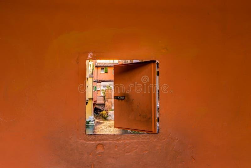 Arrosez le canal caché derrière une fenêtre en Italie image libre de droits
