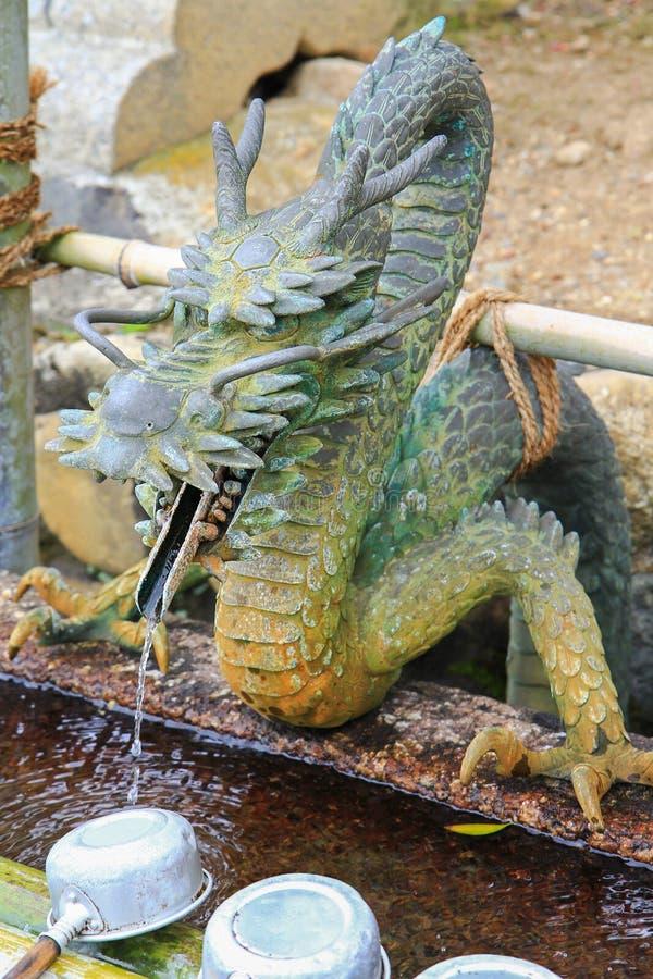 Arrosez le fonctionnement par la bouche de Dragon's pour arroser le bassin au Japon photo stock