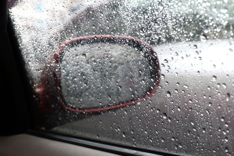 Arrosez le fond humide frais de nature de baisse avec le transparent de gouttes de pluie de l'eau du côté de miroir de voiture de photos stock