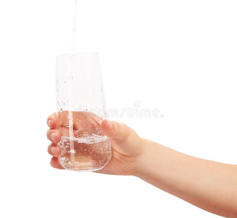 Arrosez le versement dans le plein verre à boire chez la main de la femme images stock
