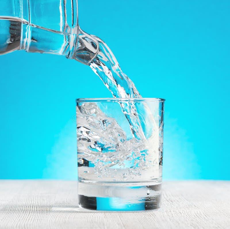 Arrosez le versement dans un verre sur le fond bleu image stock