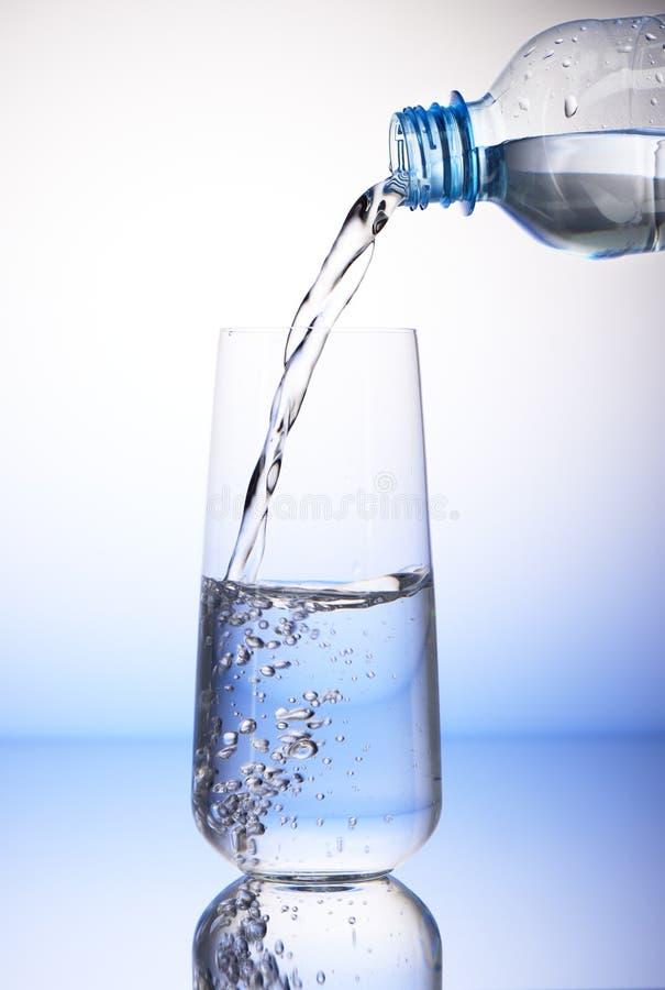 Arrosez le versement de la bouteille en plastique dans le verre à boire à moitié plein photographie stock libre de droits
