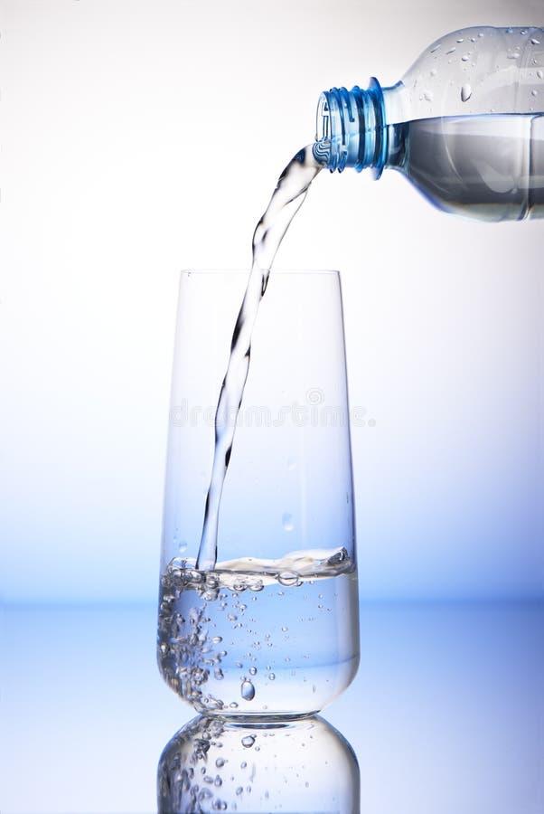 Arrosez le versement de la bouteille en plastique dans le verre à boire images libres de droits