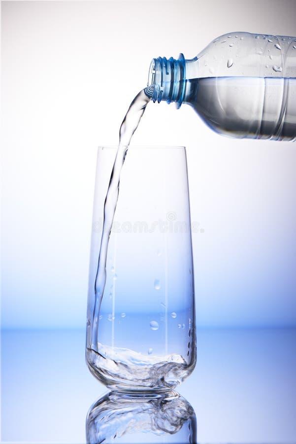Arrosez le versement de la bouteille en plastique dans le verre à boire vide photographie stock libre de droits
