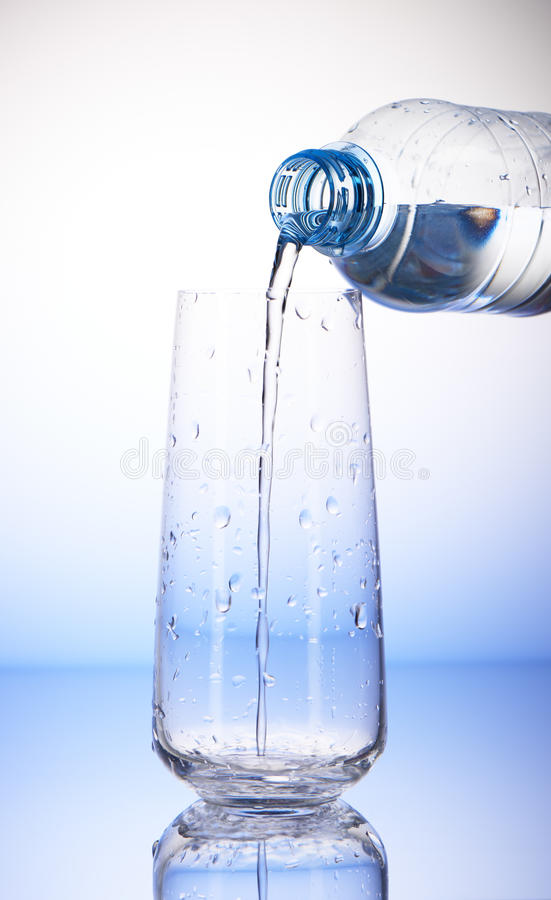 Arrosez le versement de la bouteille en plastique dans le verre à boire vide photos libres de droits