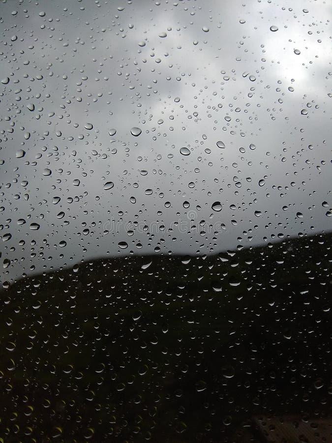 Arrosez les baisses sur le verre après la pluie Fond brouillé image stock