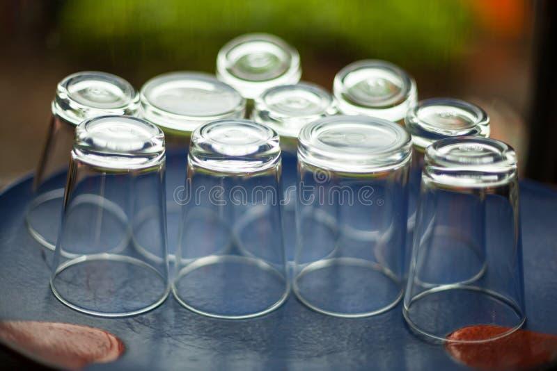 Arrosez les verres à boire à l'envers sur le backg bleu de plancher de table image libre de droits
