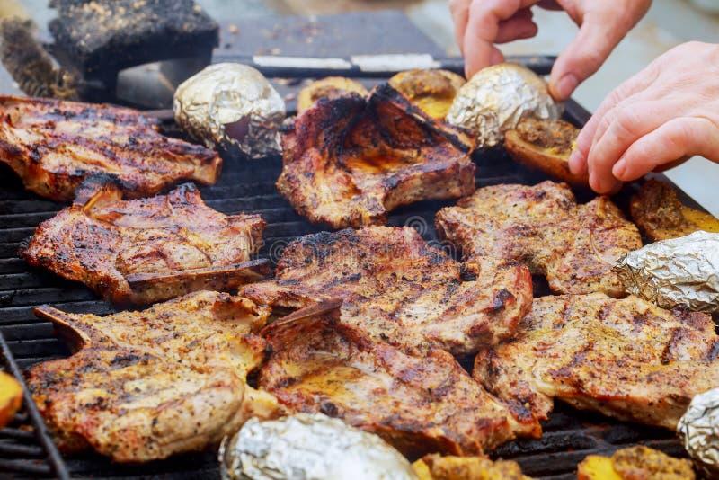 Arrostisca col barbecue il pollo arrostito e le verdure - le bistecche grigliano su fuoco immagine stock