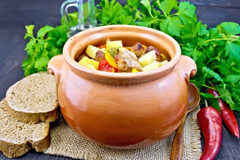Arrostisca la carne e le verdure in vaso di argilla sul bordo scuro immagine stock libera da diritti