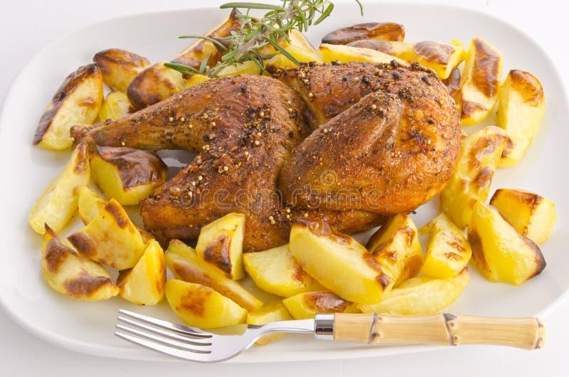 Arrosto dei polli con le patate di cottura immagine stock
