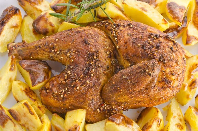 Arrosto dei polli con le patate di cottura immagini stock