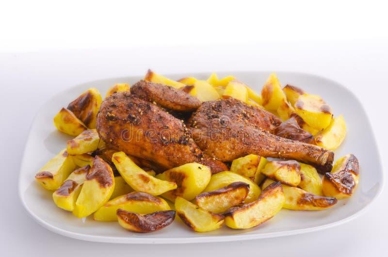 Arrosto dei polli con le patate di cottura fotografia stock