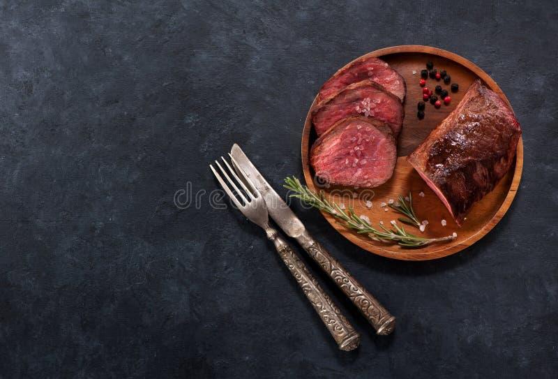 Arrosto di manzo su un piatto di legno con le spezie ed i rosmarini, su un fondo nero concreto fotografie stock libere da diritti
