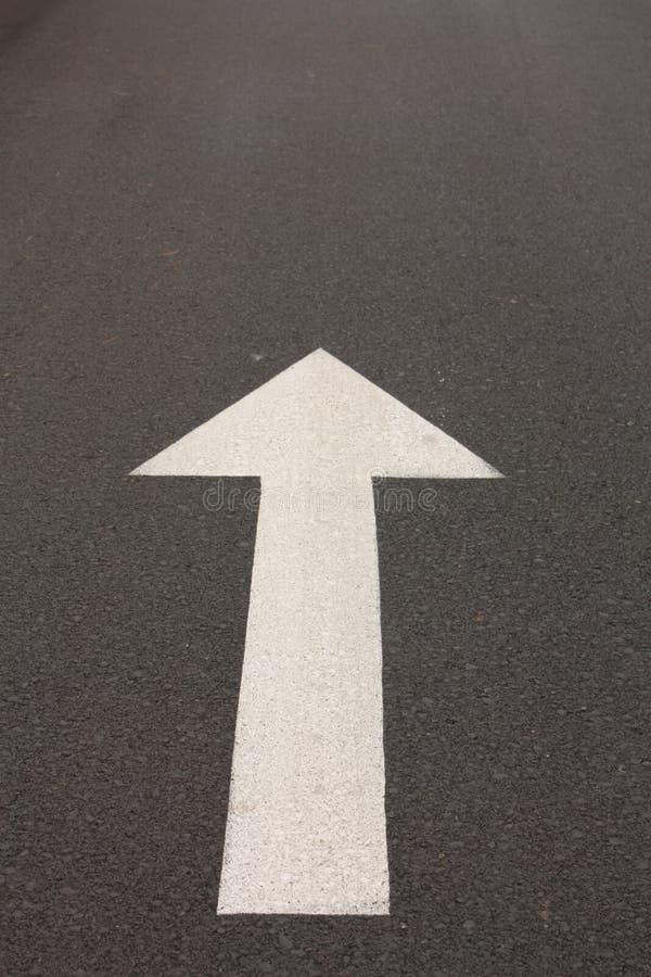 Arrow on the asphalt. Go ahead. Go straight. Traffic sign painted on the pavement royalty free stock photo