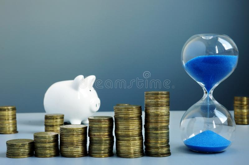 Arrow from coins stack and hourglass. Wealth and savings royalty free stock photos