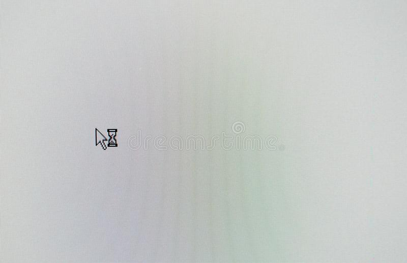 Arrow computer mouse pointer and sand glass symbol on white lcd screen. Arrow computer mouse pointer and sand glass symbol on the white lcd screen royalty free stock images