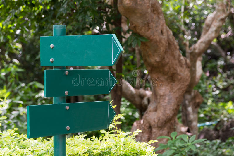 Arrow direction green signpost in park. stock photos