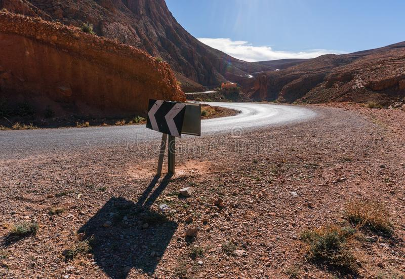 Arrow direction sign at Picturesque Serpentine mountain road in Gorges Dades in high Atlas, Morocco.  royalty free stock images