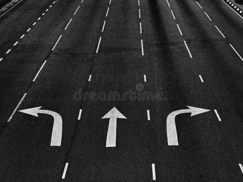 Arrow directions on asphalt road at a junction in black and white royalty free stock photo