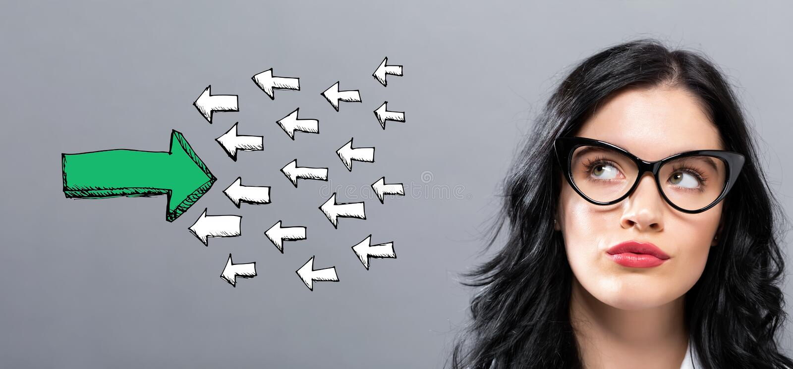 Arrow facing in a opposite direction with young businesswoman. In a thoughtful face royalty free stock image