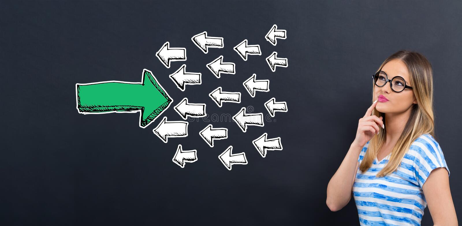Arrow facing in a opposite direction with young woman. In front of a blackboard stock photo