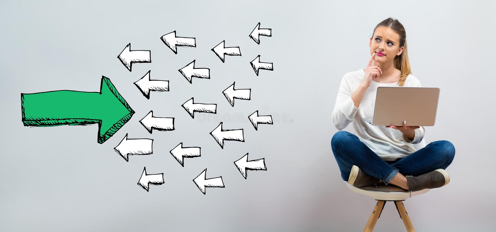 Arrow facing in a opposite direction with young woman using her. Laptop on a grey background stock image