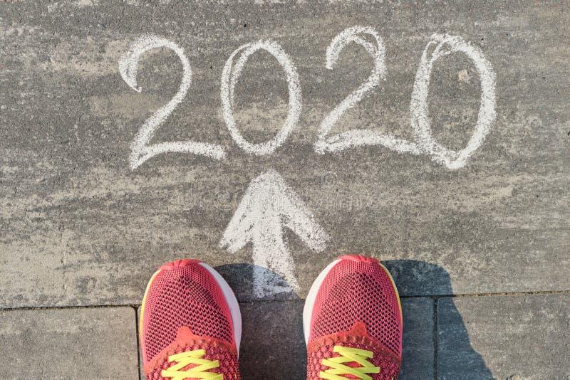 2020 arrow forward, written on gray sidewalk with woman legs in sneakers, top view.  royalty free stock photo