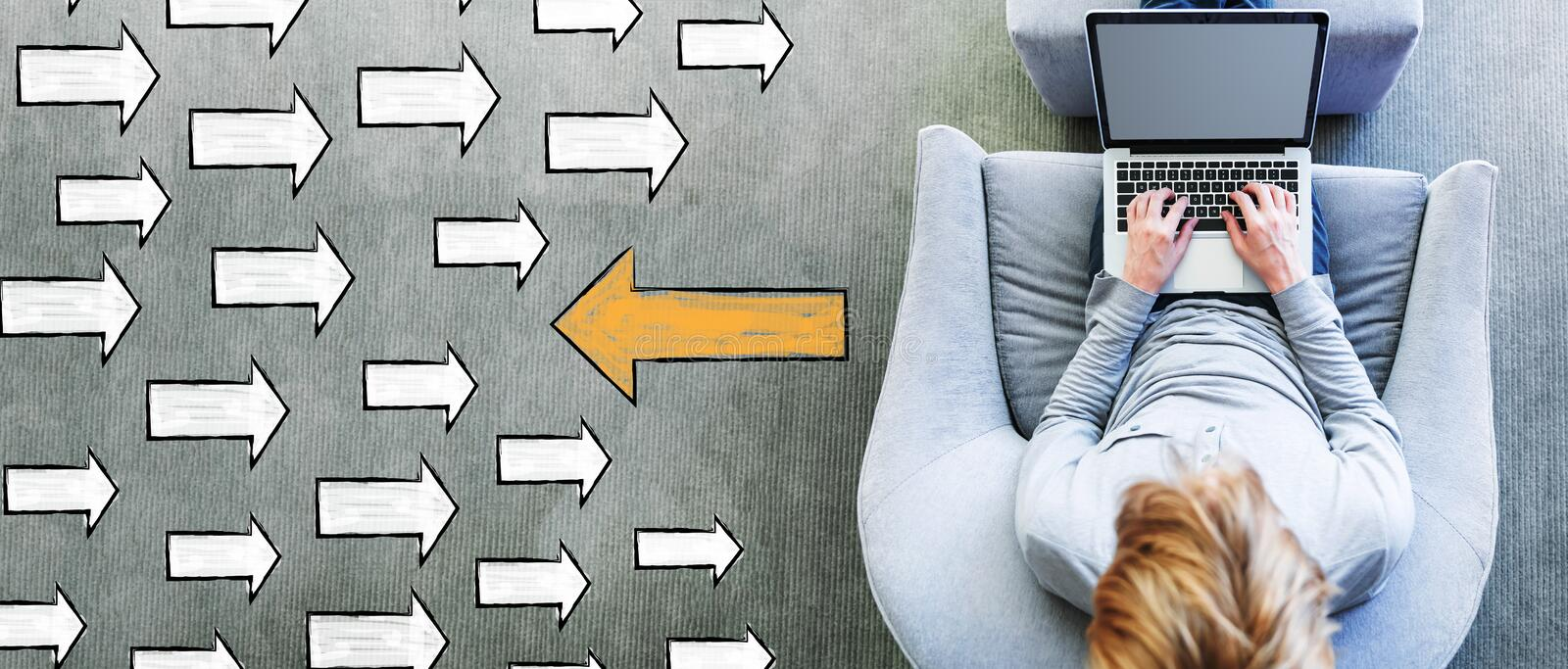 Arrow going in a opposite direction with man using a laptop. In a modern gray chair stock photography