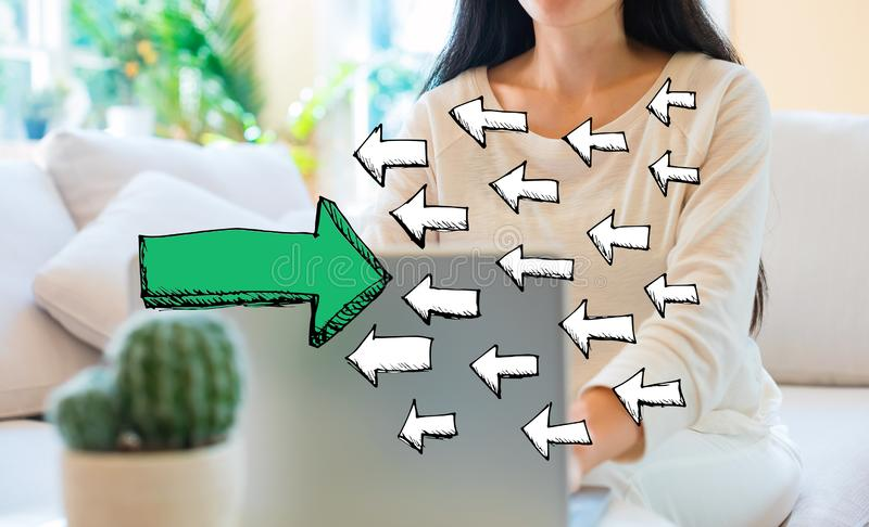 Arrow going in the opposite direction with woman using her laptop. In her home office royalty free stock photos