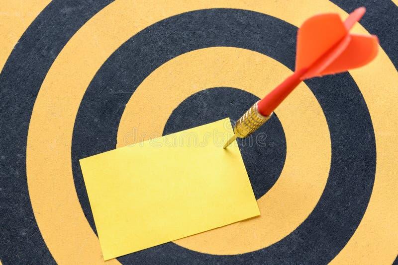 Arrow hitting yellow blank note over in bullseye on dartboard royalty free stock image