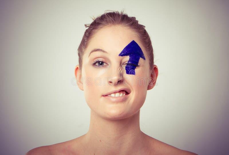 Arrow painted over eye stock photography