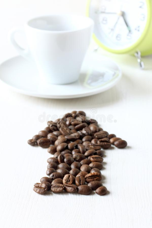 Time to drink natural drink. Arrow from roasted coffee-beans indicates a blurred cup with the clock royalty free stock image