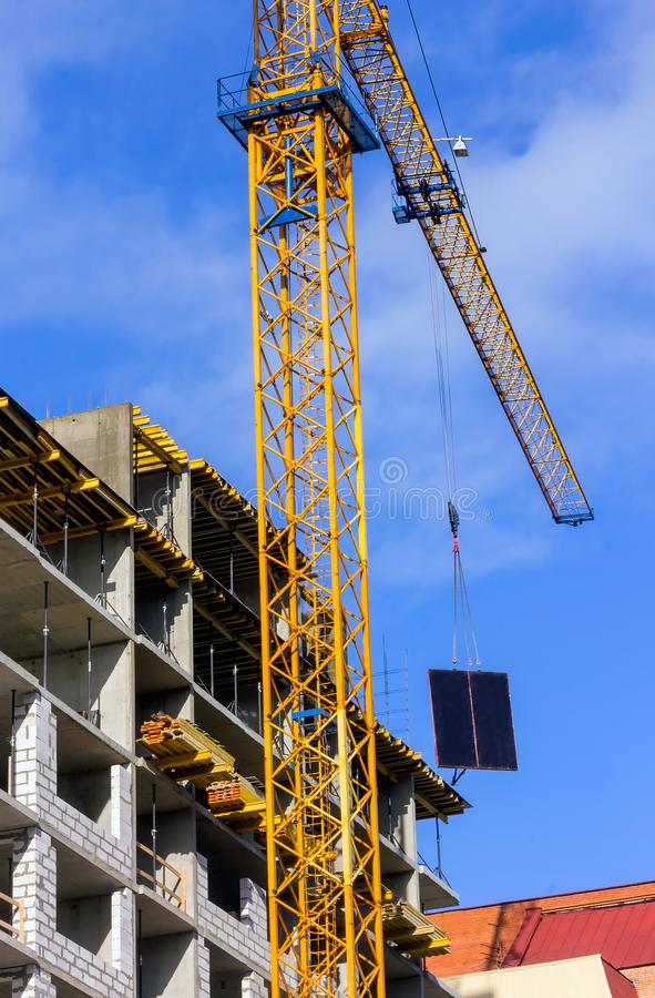 Construction of a new house using a tower crane with an arrow royalty free stock photo